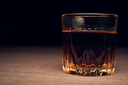 Glass of whiskey on table photo