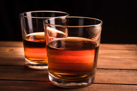 Glasses of whiskey on wooden table photo