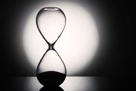 Hourglass clock on dark background photo
