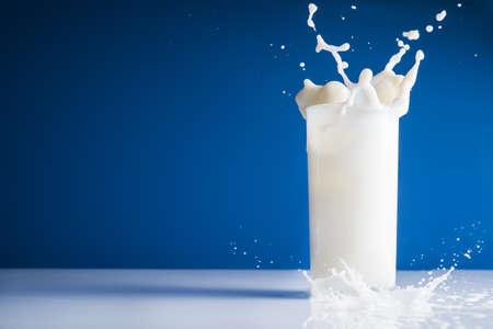 Milk splash en verre sur fond bleu Banque d'images - 38746624