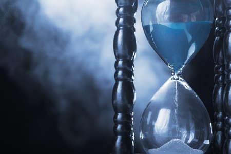 reloj de arena: Reloj reloj de arena y el humo sobre fondo oscuro