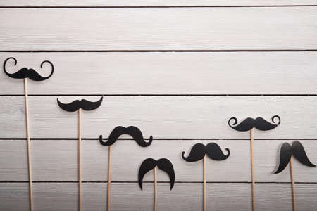 photo of accessories: Wedding accessories set moustache on white table Stock Photo
