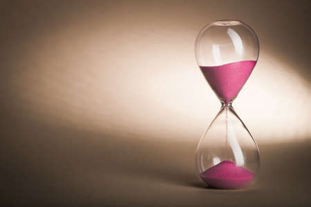 Hourglass clock on yellow vintage background Stock Photo