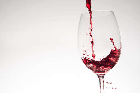 wine tasting: Pouring red wine into glass on white background