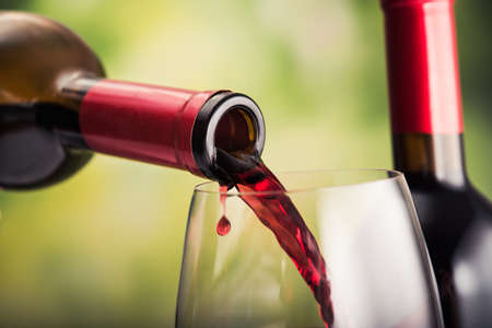 Poured red wine into glass on natural background