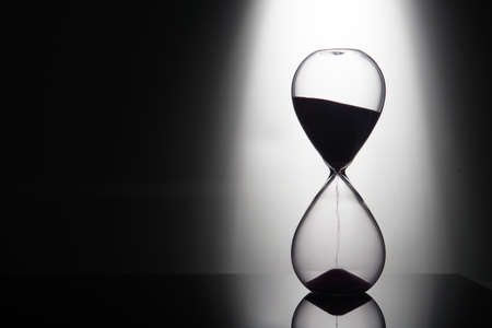 hourglass: hourglass on the background of the light beam from behind Stock Photo