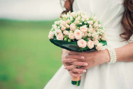 bride dress: Bride holding a wedding bouquet of roses flowers
