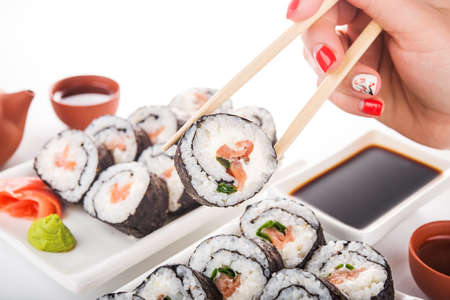 sushi: Woman hold sushi roll on background