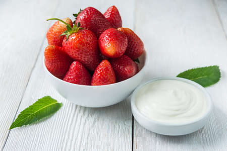 cream: Fresh red strawberries with cream om white wood table. Easy dietary breakfast. Stock Photo