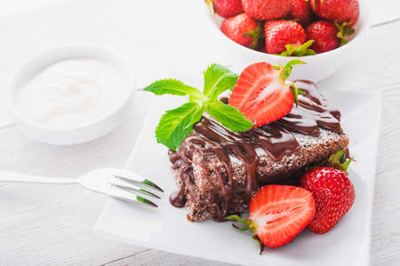 dessert fork: Chocolate cake with fresh strawberries and inches. Dessert food photography.