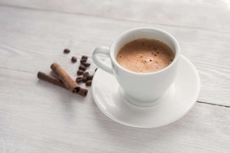 Hot cappucino cup on white table