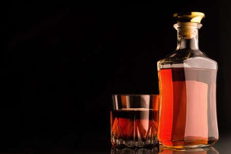botella de whisky: botella de whisky de oro y vidrio sobre fondo oscuro.