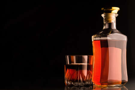 Gold whiskey bottle and glass on dark background.