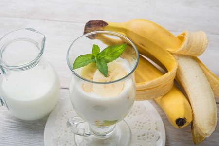 banane: banane cocktail avec des feuilles de menthe sur fond blanc en bois