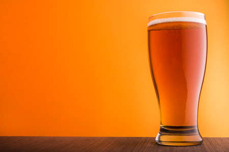 background yellow: Glass of light beer on yellow background Stock Photo