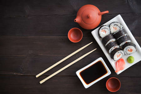 sushi restaurant: Sushi rolls with salmon and hot tea ceremony on black wooden table