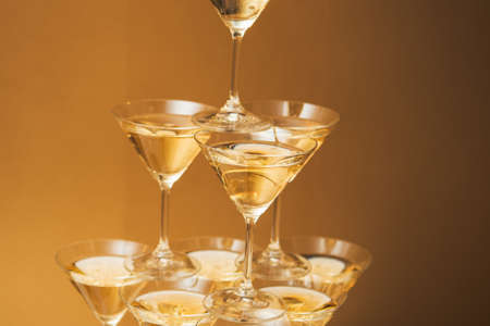 wedding table decor: Pyramid of glasses of champagne. Drinks at the party. Golden colors.