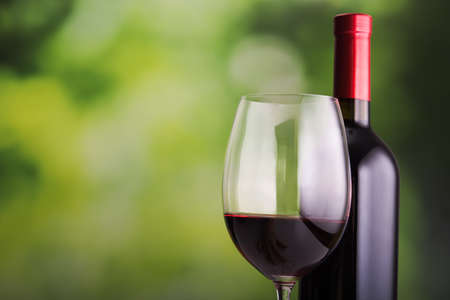 table glass: Glass of wine and bottle on green background