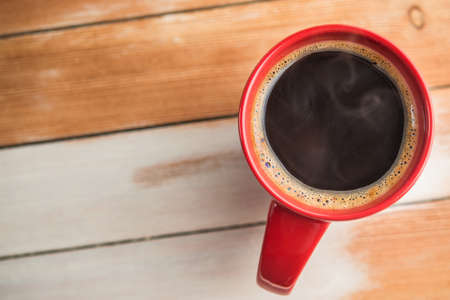 red coffee cup on wood table Archivio Fotografico