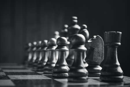 king and queen: Chess pieces on the board. Black wood background behind.