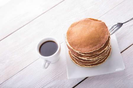 hot cakes: crepes sabrosas con la taza de café en la mesa de madera blanca