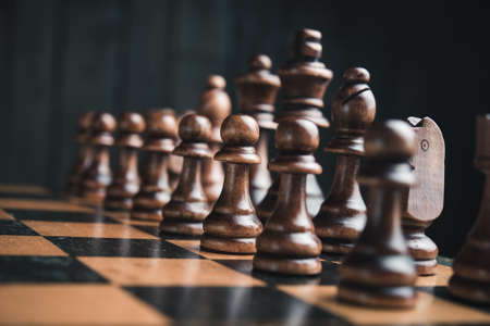 strategic: Chess pieces on the board. Black wood background behind.