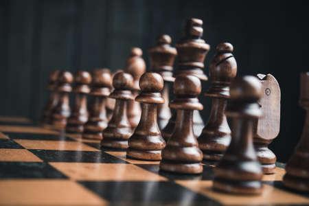 Pièces d'échecs sur le plateau. Noir fond en bois derrière.