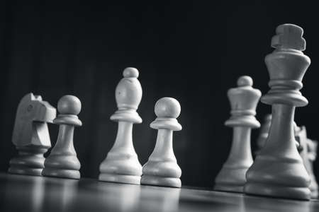 battle plan: Chess pieces on the board. Black wood background behind.