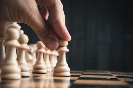 Šachové figurky na palubě. Černé dřevo pozadí za sebou. Reklamní fotografie