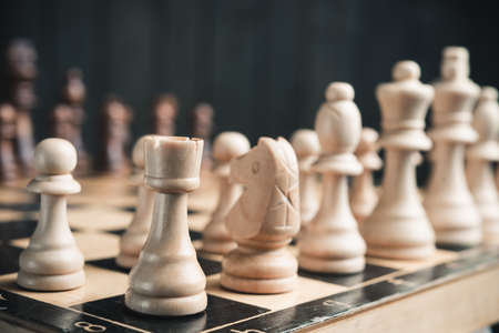 pawn to king: Chess pieces on the board. Black wood background behind.