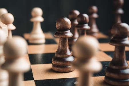 보드에 체스 조각입니다. 검은 나무 배경 뒤에.