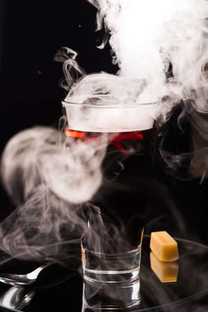fume: hot mulled wine with fume on a black background Stock Photo