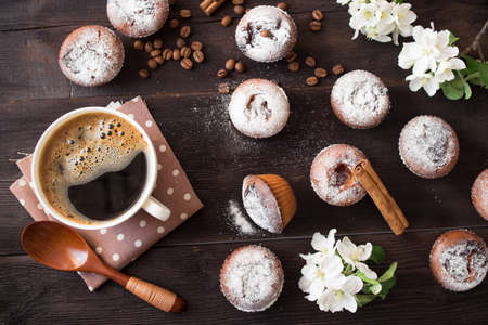 teacake: coffee cup, tasty seedcake and flower blossom on brown table Stock Photo