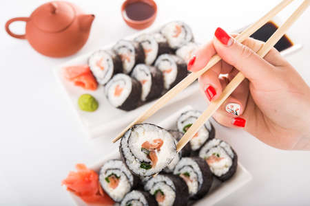 woman holding sushi roll with chopsticks on white background