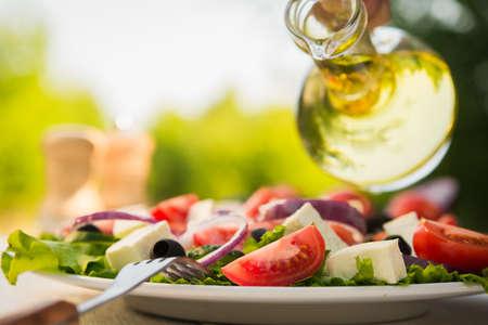 Frischer Caesar-Salat auf weißen Holztisch im Garten. Kochen im Freien.