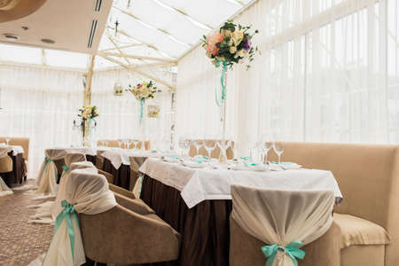 banqueting: banqueting hall. serving table. decorated wedding chairs in row. wedding luxury party place. restaurant interior