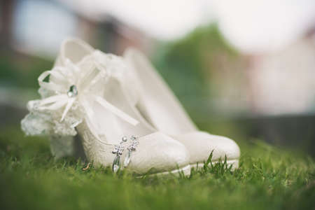 macro photo of white wedding shoes with ornamentation at green grass