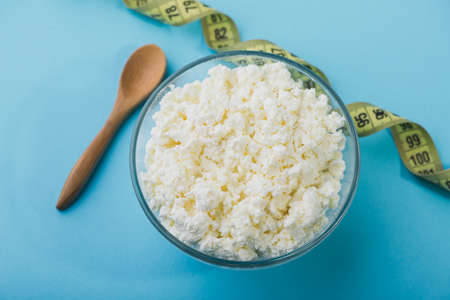 Fresh cottage cheese in a glass bowl on blue table. Diet background. healthy food Stock Photo