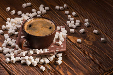 vintage coffee cup with hot dring and tasty marshmallow, roasted beans on wooden table