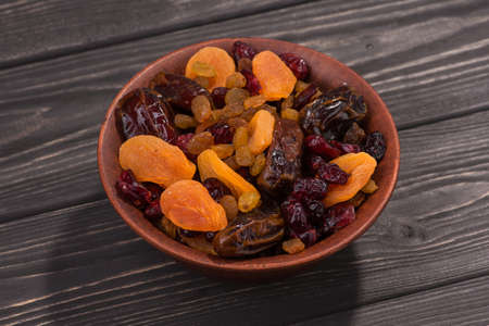 Mix of dried fruit in clay bowl, stand on wooden black table