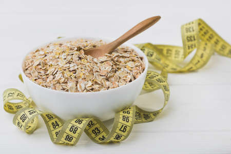 uncooked grain of oatmeal in white bowl with measuring tape. diet concept. healhy food