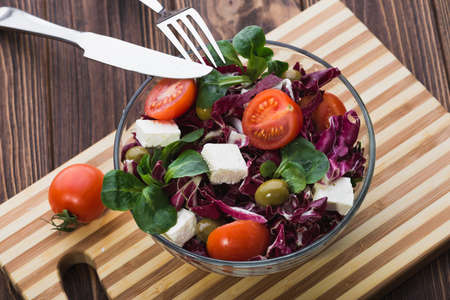 fresh salad in glass bowl with tomato, chees feta and green leaves on wooden table. diet background