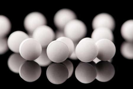 white tablets on black glass background. medical pharmacy