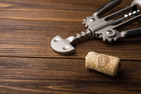 uncork: wine corkscrew on wooden table. alcohol background