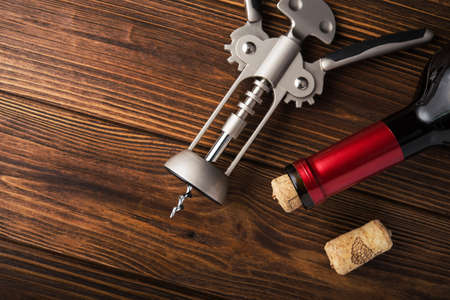 white wine: wine corkscrew and bottle on wooden table. alcohol background