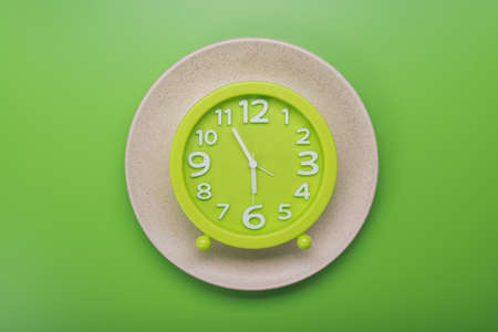 morning blue hour: clock with measuring tape. diet concept. top view green background
