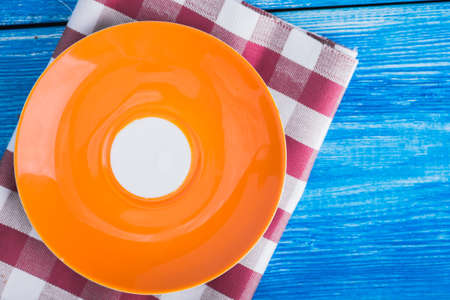vintage dishware: colored empty plate on napkin and blue wood table. top view