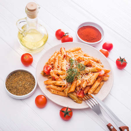 delicious penne pasta on wood white table. tasty italian dinner.