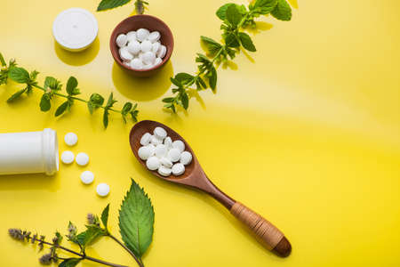 Herbal medicine pills with leaf and bottle on yellow background. top view Stock Photo