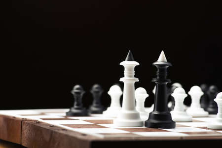pawns: Black and white chess king on the board, black background